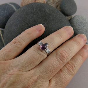 Artisan made one of a kind pink tourmaline teardrop ring on an oxidized textured sterling silver soft square band by Mikel Grant Jewellery.  Displayed on a hand.