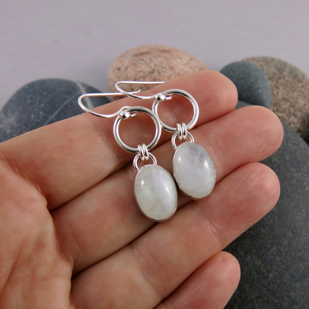 Artisan made rainbow moonstone joy drop earrings in sterling silver by Mikel Grant Jewellery. Displayed on a hand.