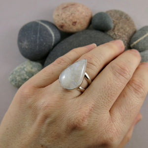 Artisan made rainbow moonstone teardrop ring on a double sterling silver band by Mikel Grant Jewellery.  Displayed on a hand.