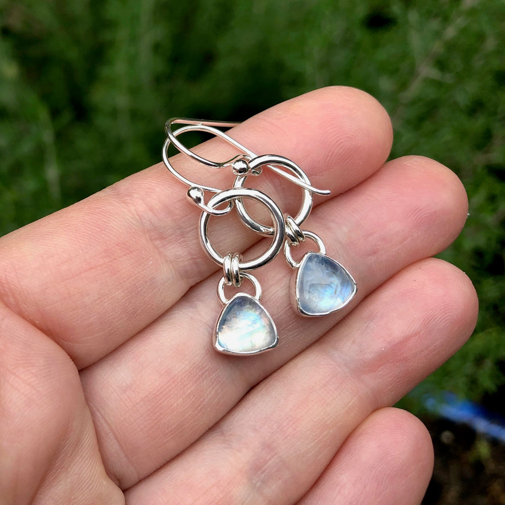 Artisan made moonstone joy drop earrings in sterling silver by Mikel Grant Jewellery.  Displayed on a hand.