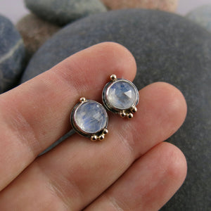 Artisan made rose cut moonstone stud earrings in sterling silver with gold details by Mikel Grant Jewellery.  Displayed on a hand.