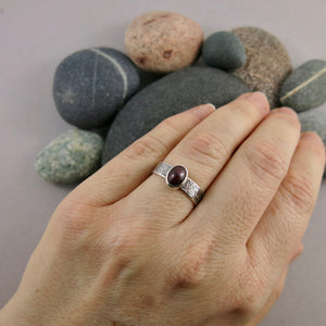 Artisan made natural ruby on an oxidized textured sterling silver soft square ring by Mikel Grant Jewellery.  Displayed on a hand.