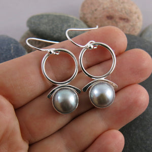 Artisan made silvery-grey button pearl joy drop earrings in sterling silver by Mikel Grant Jewellery.  Displayed on a hand.