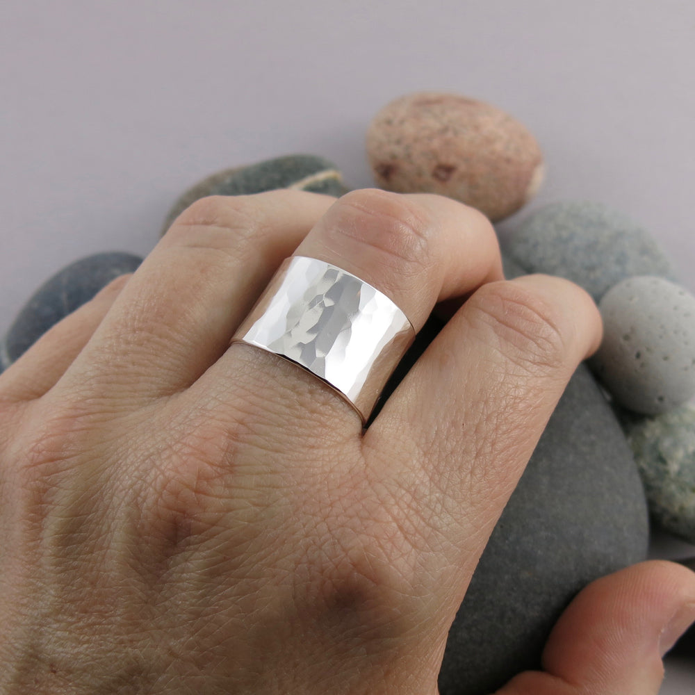 The Shimmer Ring by Mikel Grant Jewellery: an artisan made simple textured wide sterling silver ring band.   Displayed on a hand.