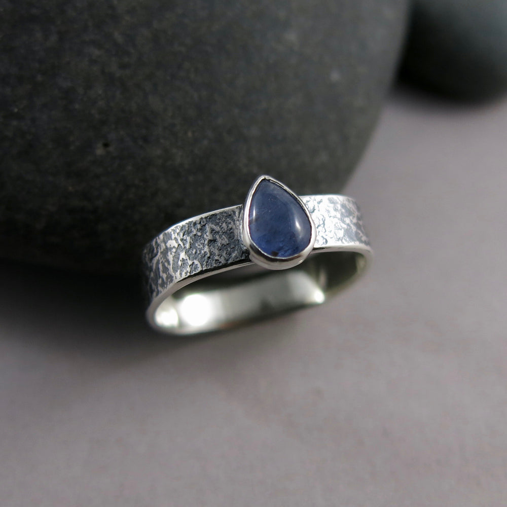 Artisan made tanzanite teardrop ring on an oxidized textured sterling silver soft square band by Mikel Grant Jewellery.