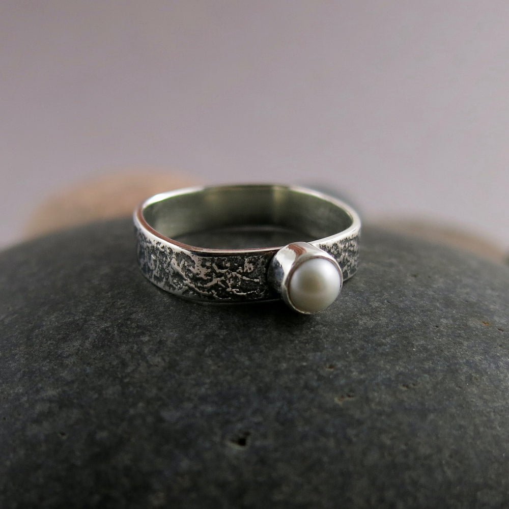 Artisan made pearl ring.  Tiny freshwater pearl on an oxidized textured soft square sterling silver band by Mikel Grant Jewellery.