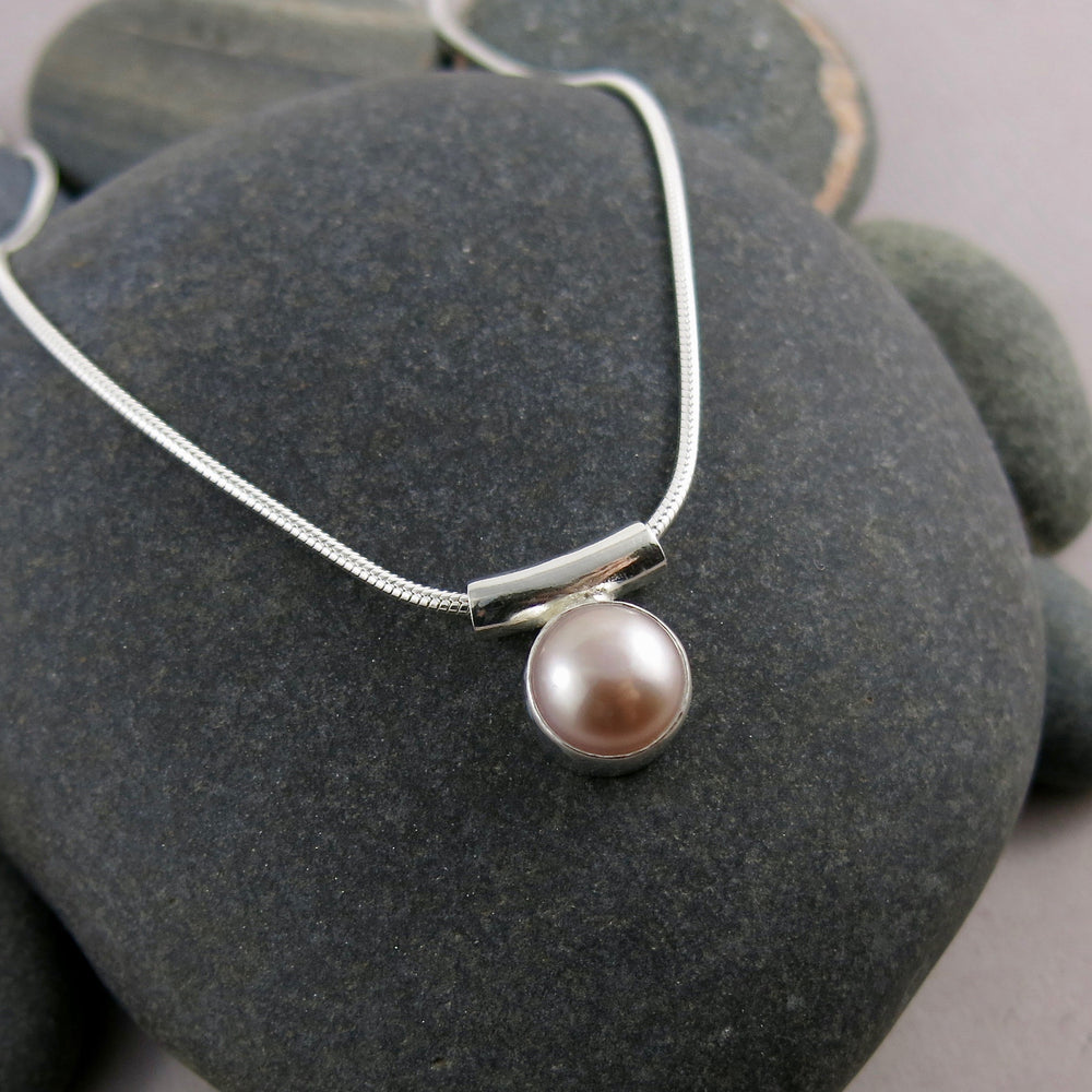 Pearl solitaire necklace by Mikel Grant Jewellery. Pink button pearl in sterling silver.