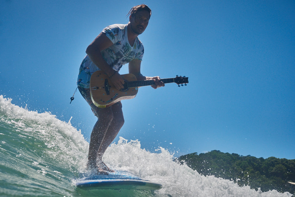jamming on a wave - playing guitar surfing