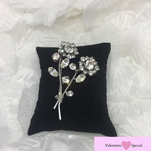 A stunning, vintage silver tone brooch with white rhinestone detail