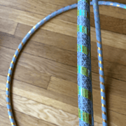 "<img src=""MultiMorph-Spiral-Reflective-Hoop-by-Autumn-Flow.jpg""alt=""two hula hoops on a wooden floor featuring blue, yellow, orange and teal glitter reflective tape in a spiral pattern on a hula hoop"""