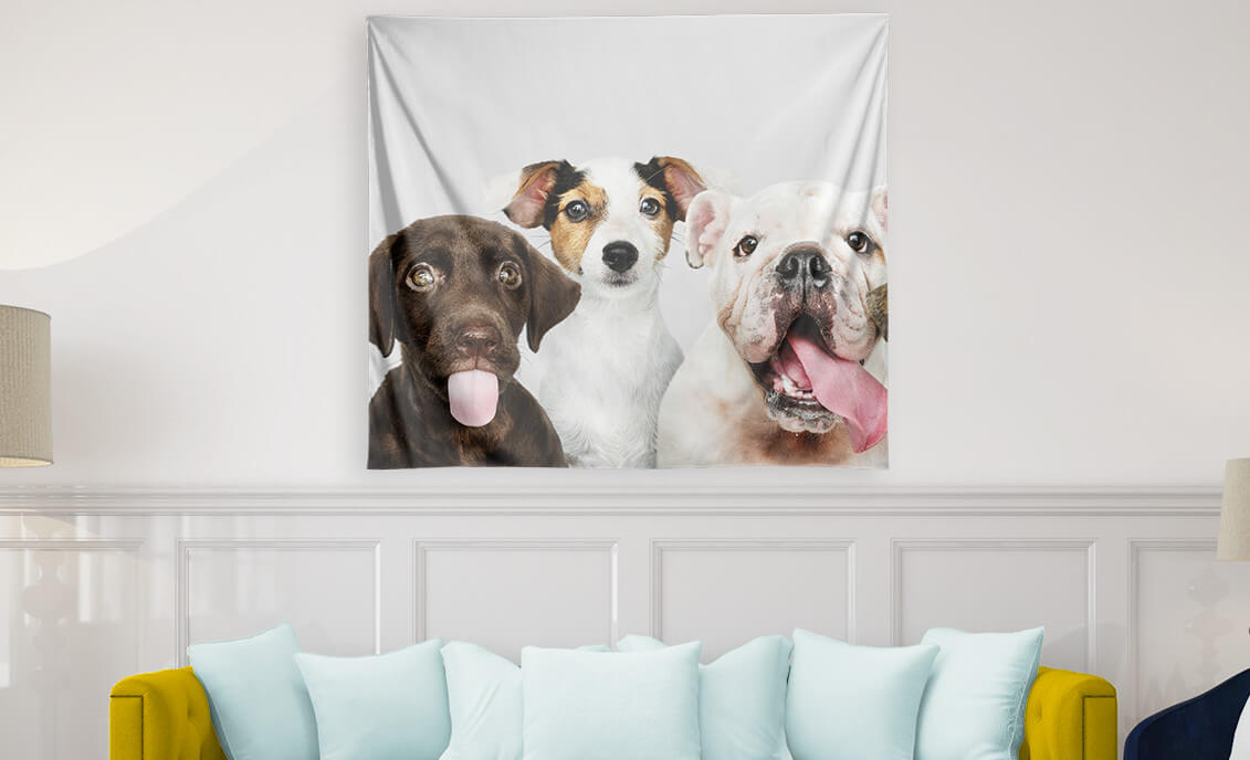 A custom tapestry with puppies on a wall behind a sofa