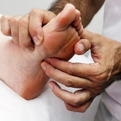 Therapist performing Reflexology on someone's foot.