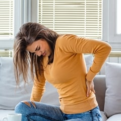 Woman Sitting in a Sofa Having Back Pain