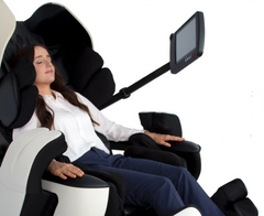 Lady relaxing in a massage chair with the remote control adjusted.