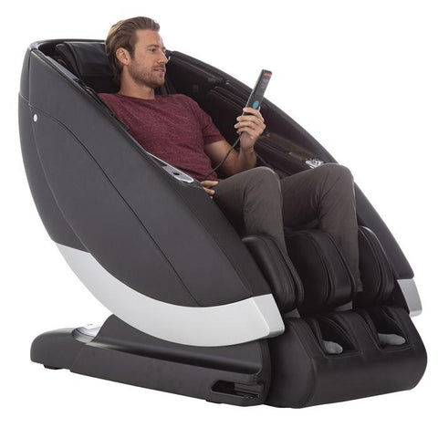 Human Touch Super Novo Massage Chair gray side view with person holding remote control