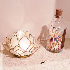 jar of matchsticks with striker, next to candle
