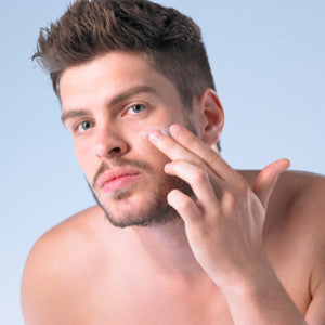 man touching his face and applying cream