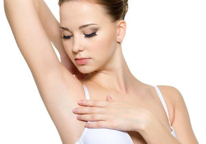 woman with upraised arm looking at her underarm