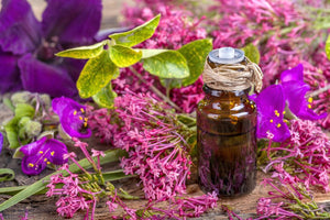 bottle of clary sage essential oil surrounded by flowers