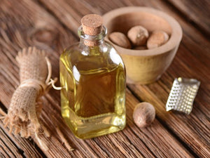 nutmeg essential oil in a clear glass bottle on a wooden table with nuts and grater in the background