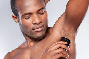 man applying deodorant to his underarm