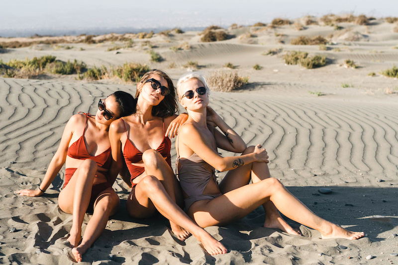 three girls in swimsuits sitting in the sand with sand dunes behind them