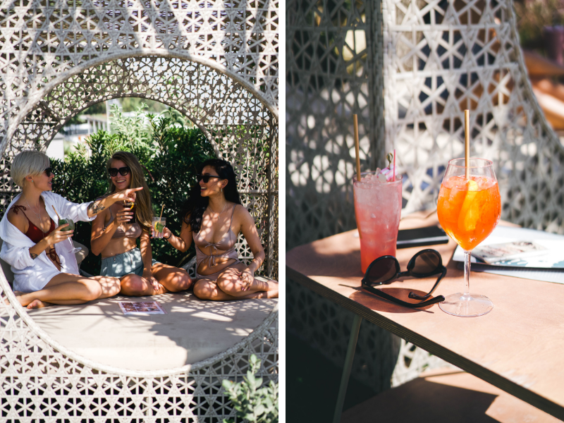 girls drinking cocktails inside a beach cabana