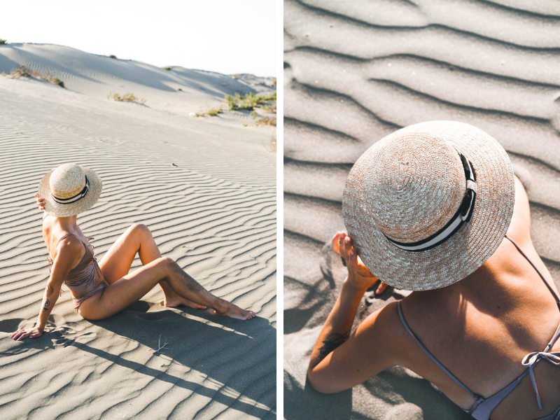 a girl in a bikini and a hat in a desert posing next to sand dunes