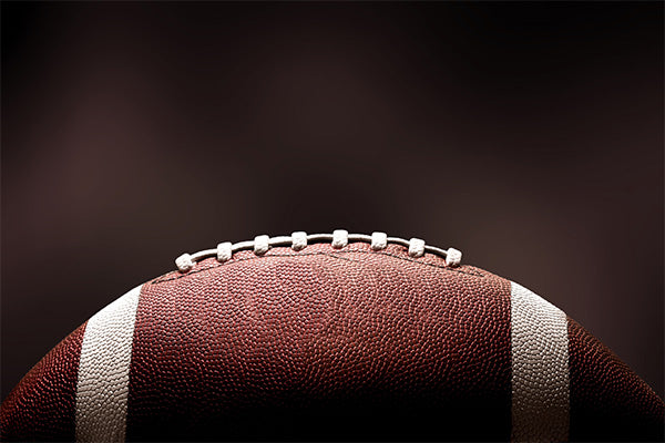 American football ball on dark background