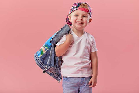 Little serious fashionable toddler boy in denim clothes and trendy cap. Isolated on pink background