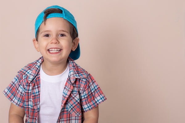 Smiling young boy wearing baseball cap