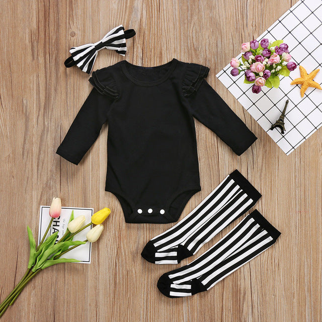 black onesie with ruffle sleeve. comes with matching striped socks and headband - Here Comes A Baby