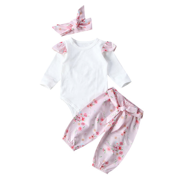 2 piece outfit with headband included. White ruffle shoulder long sleeve onesie with pink floral print long pants that match headband bow - Here Comes A Baby