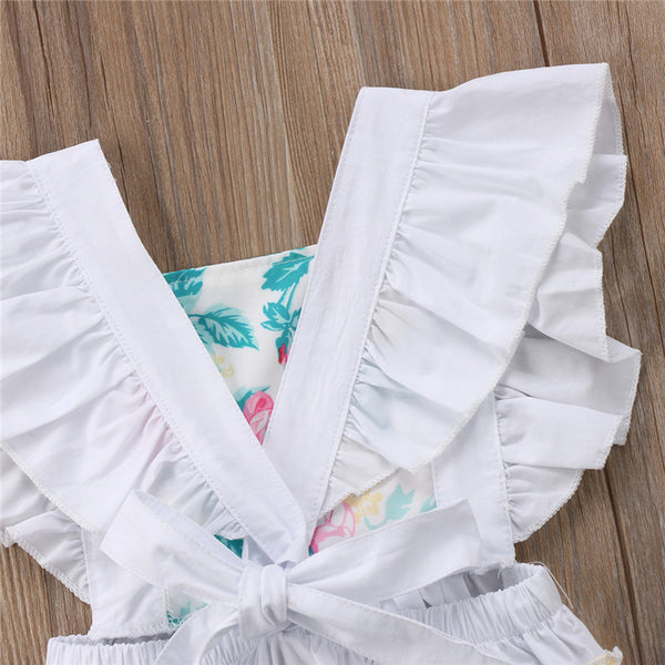 This white peekaboo floral romper is perfect when you want to put your new baby in something other than a cotton onesie. Its ruffle sleeves, crisscross back and ruffle booty add that little touch of cuteness to take it up a notch from their usual casual l - Here Comes A Baby