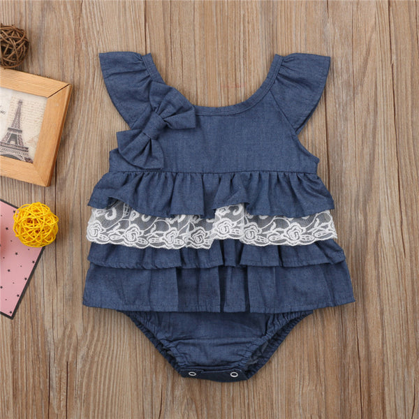 This jean style romper dress has rows of blue layers livened up by a lace ruffle and bow to dress it up and add a little color to the mix. its sleeveless tank top is great for hot weather and button bottom for easy access for diaper changes - Here Comes A Baby
