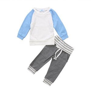2 piece sweat style set for that cooler weather on its way. Solid Blue and white long sleeve sweatshirt top with striped elbow and long grey pants with striped lining and tie waist pocket design. - Here Comes A Baby