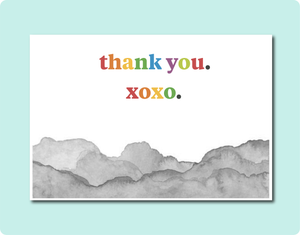 Thank You xoxo. Greeting Card with grey watercolour on bottom and text thank you and xoxo letters in different colours of the rainbow