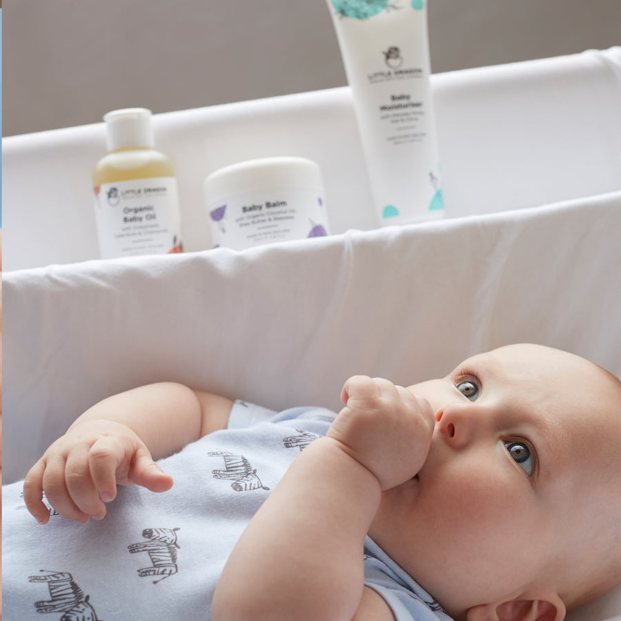 A young baby lying in his nursery along with Little Dragon Skincare products