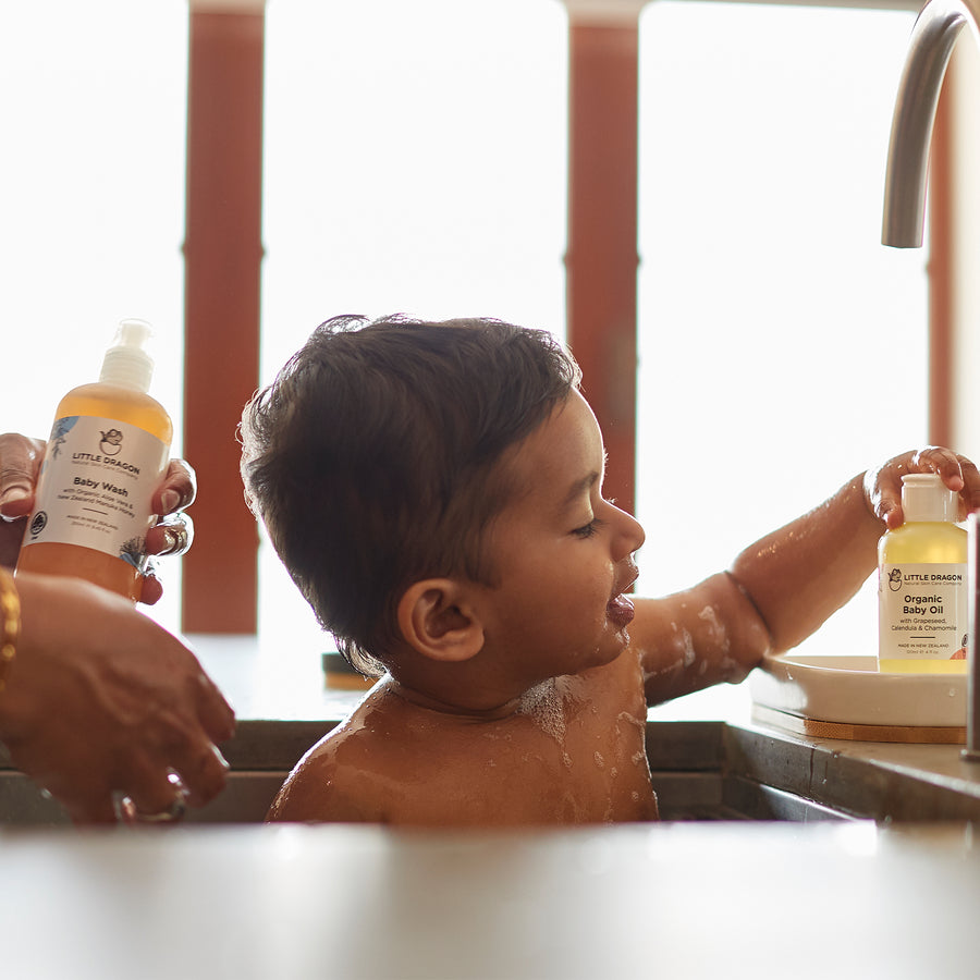 Young child takes a bath with his mother using Little Dragon baby wash and Oil