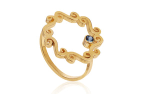 Gold open swirly ring with blue sapphire setting
