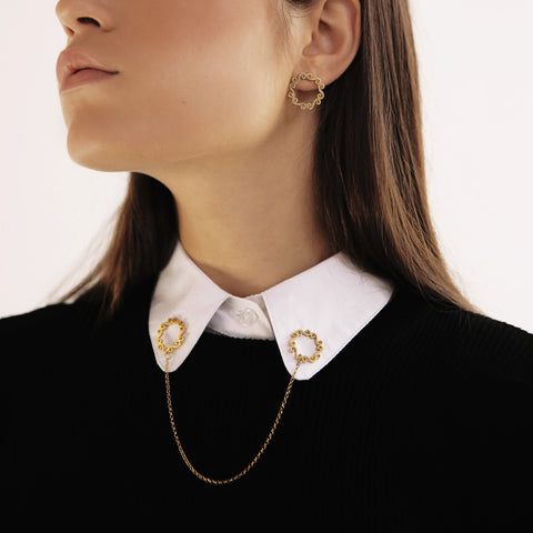 Woman wearing double gold brooch on shirt collar