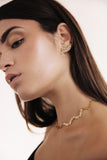 Woman wearing gold choker necklace and matching ear crawlers