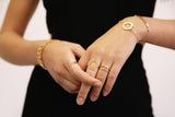 Hands wearing gold cracelets and rings