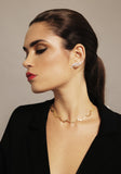 Woman with pony tail wearing gold jewellery and red lipstick