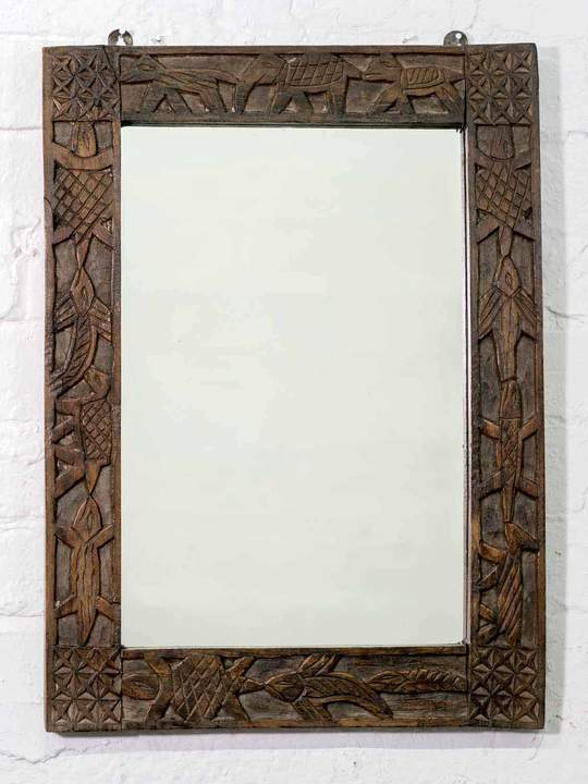 A rustic Indian wooden mirror with carved animals running around the frame.