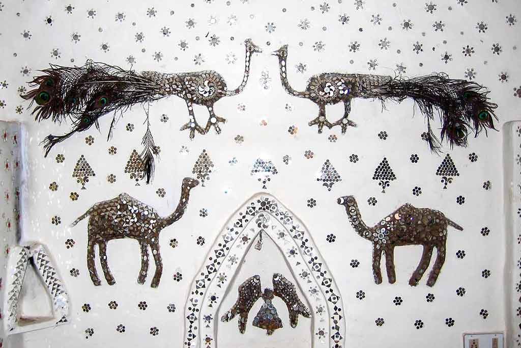 Mirrored & sequinned peacock images on a guest house wall in Jhunjhunu