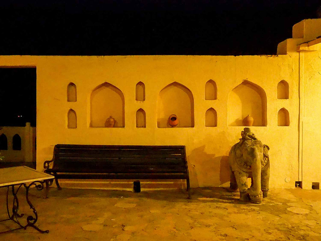 Courtyard with niches, simple clay pots and an elephant at Neemrana