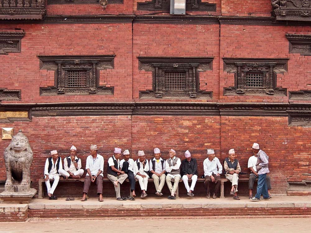 men sitting outside the royal palace, patan