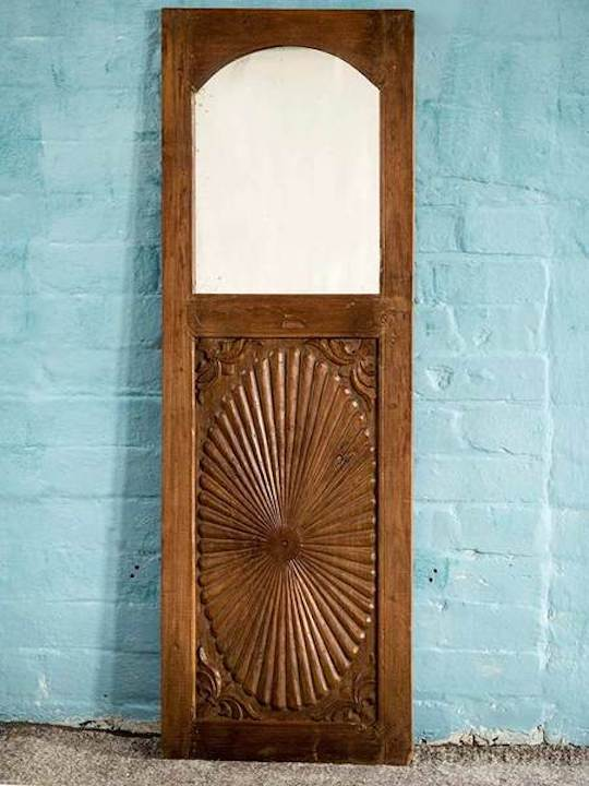 A carved Indian wooden mirror in teak coloured timber that was orginally a wardrobe door.