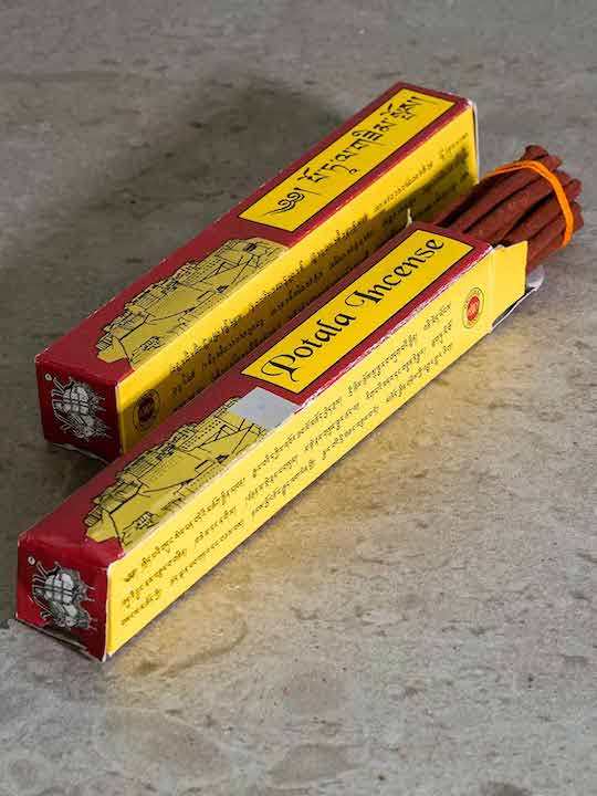 Tibetan incense in a maroon and yellow packet with a drawing of the Potala Palace.